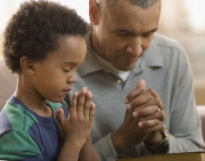 Father is teaching his son to be religious