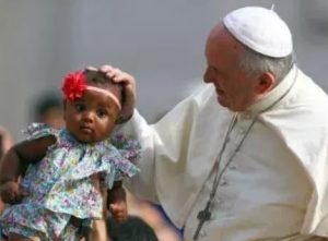 Pope Francis blessing a child in 2018