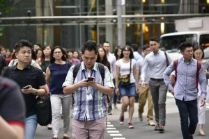 People using their phone while crossing road