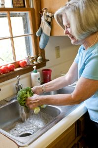 woman-washing-a-head-of-broccoli-in-her-sink