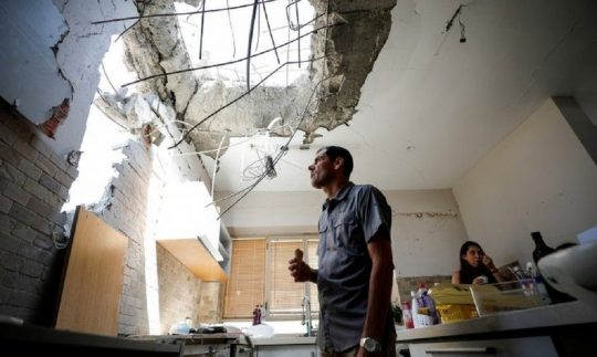 An Israeli man inspecting his house destroyed by Hamas rockets