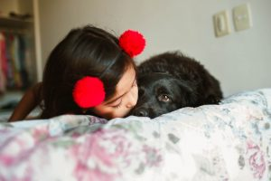 girl with hairband kissing black dog