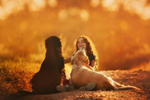 smiling girl leaning on two dogs during sunset