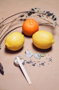 lemons and an orange lying on floor with a stick