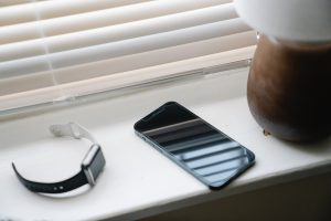 a watch and phone on white window ledge