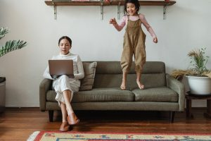 woman holding a laptop while child jumps on sofa